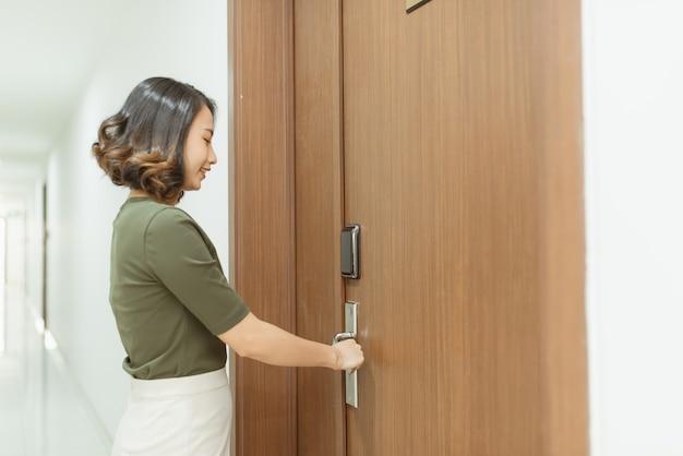Mulher abre a porta do apartamento