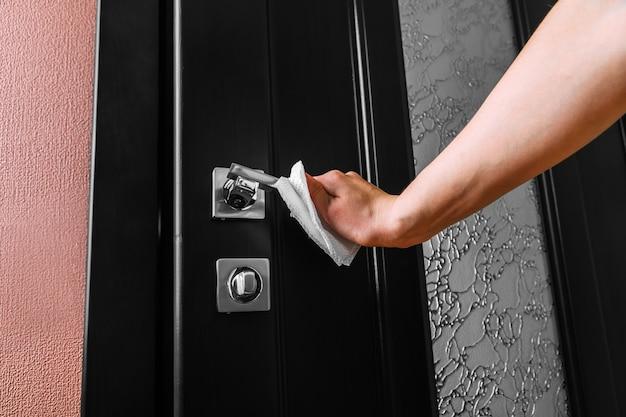Mulher abre a porta usando luvas de proteção de látex. conceito de medidas de disseminação de coronavírus.
