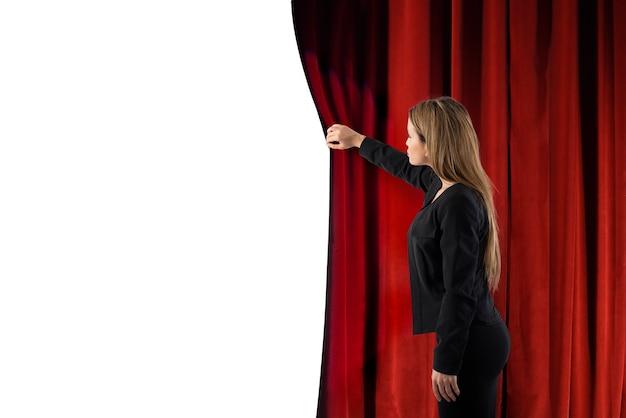 Mulher abre as cortinas vermelhas do espaço em branco do palco do teatro para o seu texto