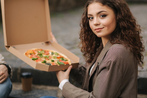 Mulher abre caixa de pizza ao ar livre