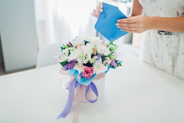 Mulher abre envelope com cartão deixado no buquê de flores em caixa de presente na cozinha. surpresa. presente para férias