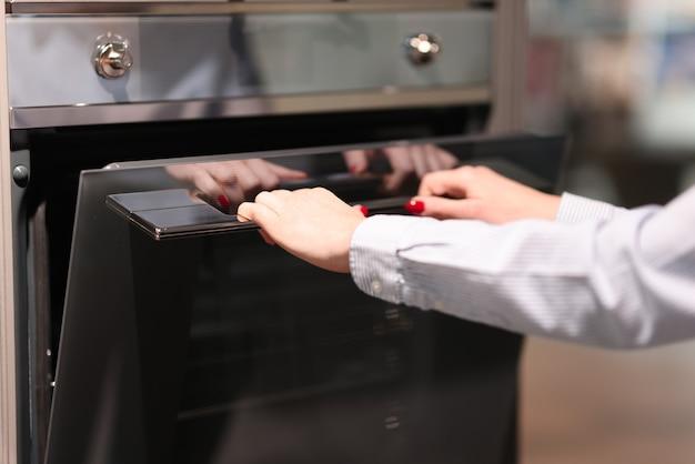 Mulher abre o forno. escolha de eletrodomésticos para o conceito de cozinha