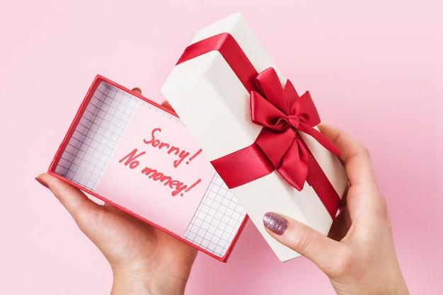 Mulher abre uma caixa com um presente em um conceito rosa sobre o tema falta de dinheiro para comprar presentes