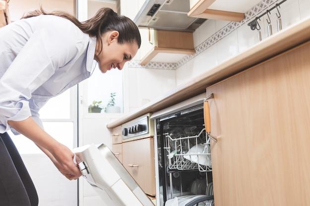 Mulher abrindo a máquina de lavar louça na cozinha do apartamento dela