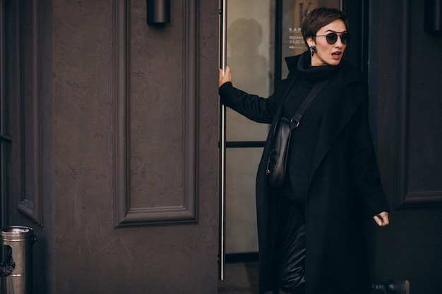 Mulher abrindo a porta de uma cafeteria