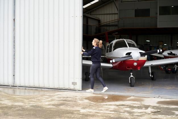 Mulher abrindo a porta do hangar onde há vários aviões