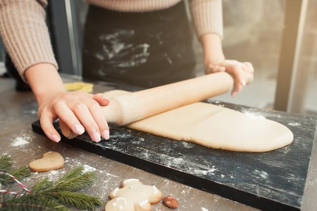 Mulher abrindo massa na cozinha