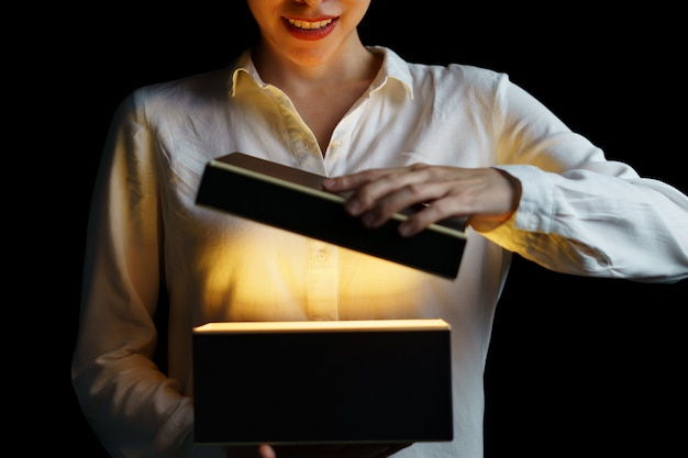 Mulher abrindo uma caixa com luz dourada significa algo emocionante por dentro.