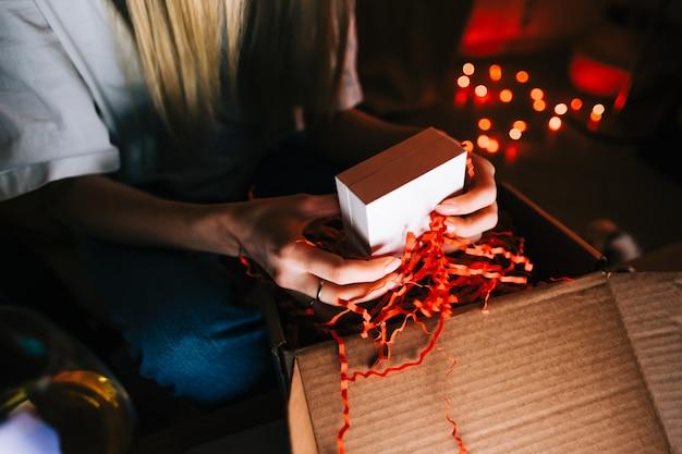 Mulher abrir o presente durante a videochamada no laptop e beber vinho, usar a tecnologia para se comunicar com amigos ou família.
