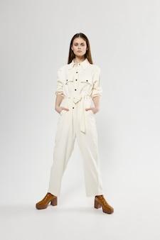 Mulher abriu as pernas e macacões brancos estilo de roupas da moda.