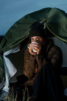 Mulher acampando à noite com uma xícara de chá