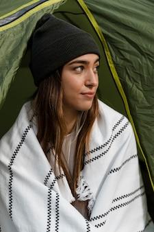 Mulher acampando e olhando para longe