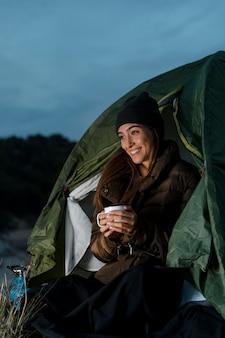 Mulher acampando e segurando uma xícara de chá