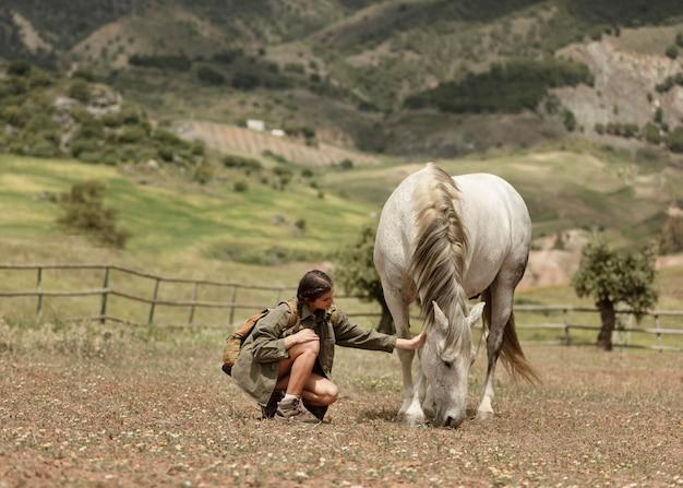 Mulher acariciando o cavalo, tiro completo