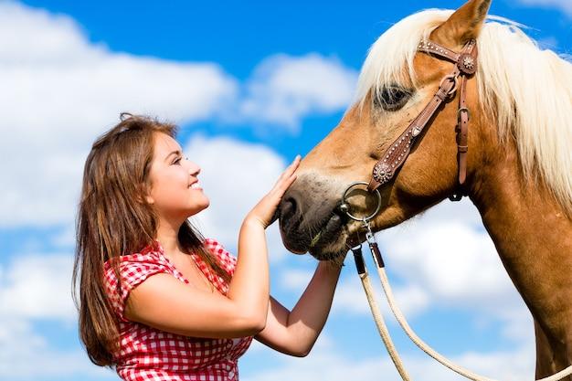 Mulher acariciando um cavalo em uma fazenda de pôneis