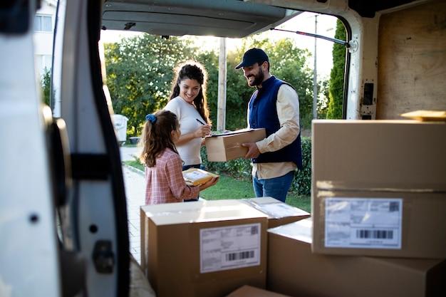 Mulher aceitando pacotes de entregador ou mensageiro.