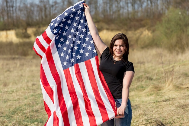 Mulher acenando a bandeira dos eua fora durante o dia da independência