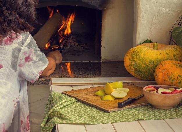 Mulher acende um fogo no forno
