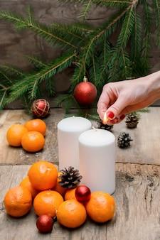 Mulher acendendo velas composição de natal com tangerina frutas mesa de madeira natal ano novo