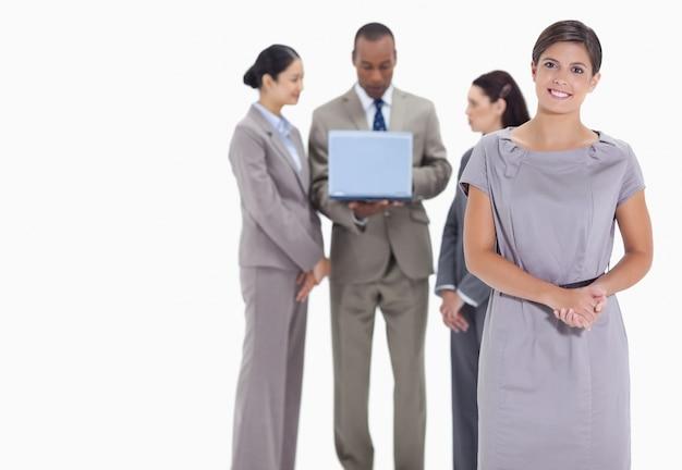 Mulher acolhedora e colegas de trabalho com um laptop no fundo