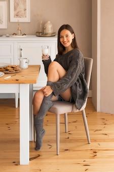 Mulher aconchegante na cadeira segurando um copo de leite