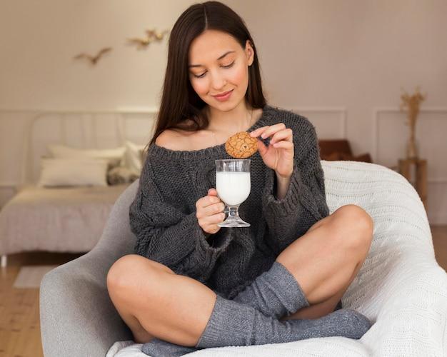 Mulher aconchegante na poltrona com biscoito e leite