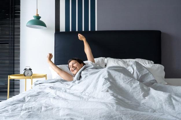 Mulher acorda de bom humor em um apartamento elegante. estica com um sorriso começando o dia
