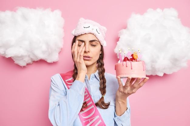 Mulher acorda muito cedo em seu aniversário contras rosto com a mão fecha os olhos segura um bolo festivo usa uma máscara de dormir na testa tem duas tranças penteadas isoladas em rosa