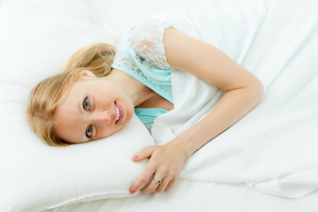 Mulher acordando em sua cama
