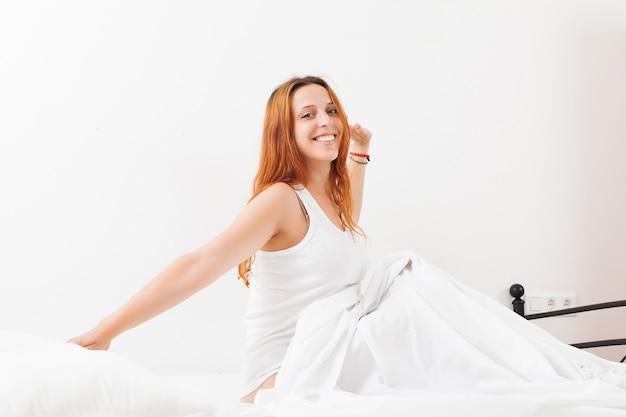 Mulher acordando na folha branca em sua cama em casa