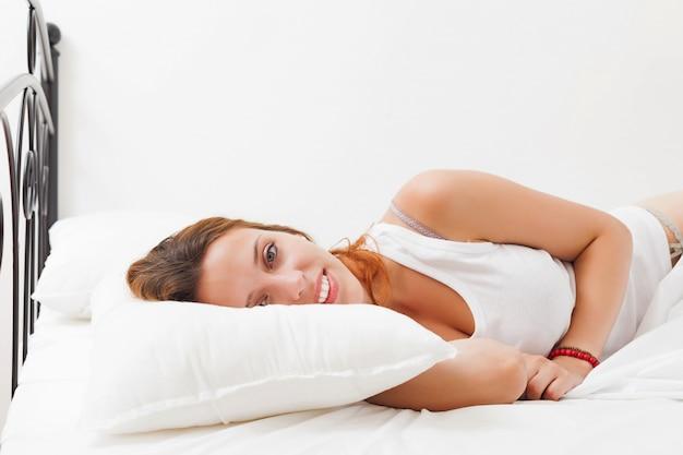 Mulher acordando na folha branca na cama em casa