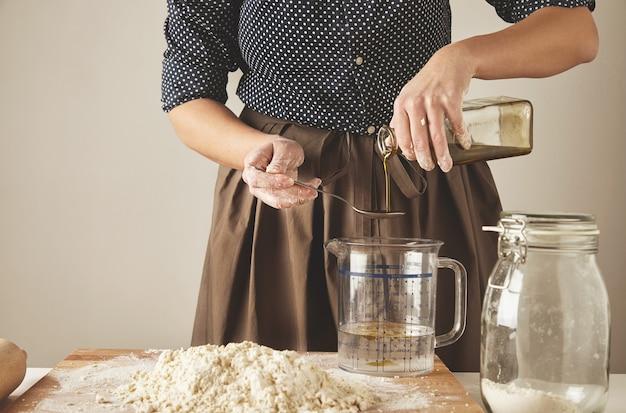 Mulher adiciona um pouco de azeite de oliva em água em copo medido atrás da mesa com ingredientes de massa, para fazer macarrão ou bolinhos.