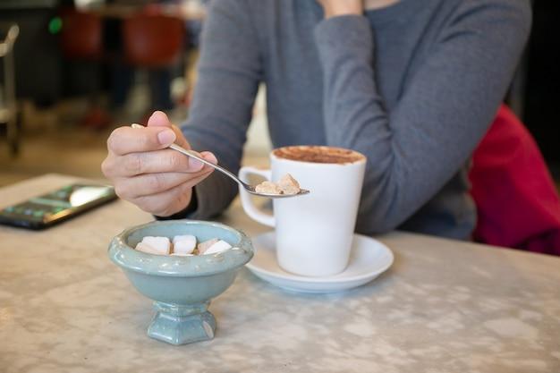 Mulher, adicionando cubos de açúcar no café em cima da mesa.
