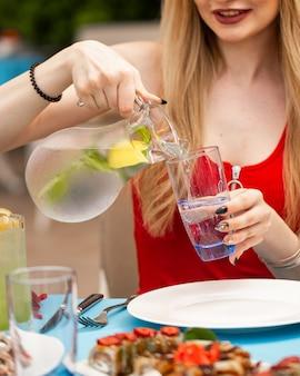 Mulher adicionando limonada de jarra em vidro.