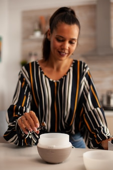 Mulher adicionando óleos essenciais ao difusor para aromaterapia