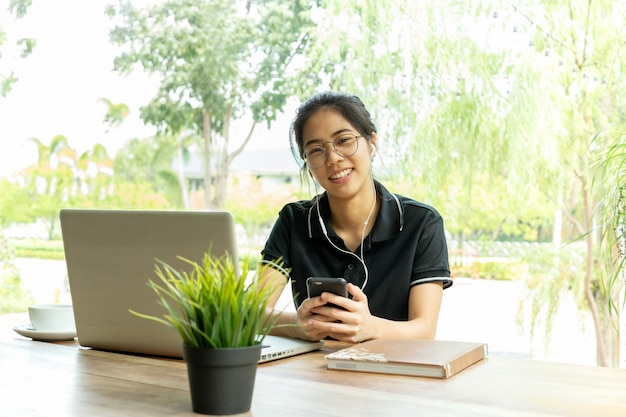 Mulher adolescente asiática com fone de ouvido e laptop localização no café.