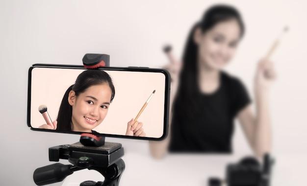 Mulher adolescente asiática sentada na frente da câmera transmitindo ao vivo como influenciadora de blogueira de beleza