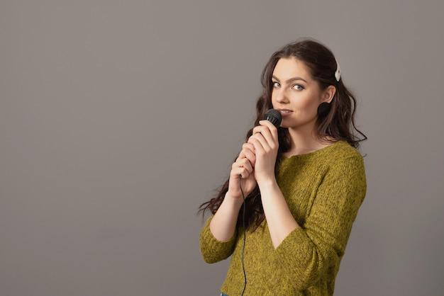 Mulher adolescente atraente falando com um microfone contra uma superfície cinza, apresentação de discurso