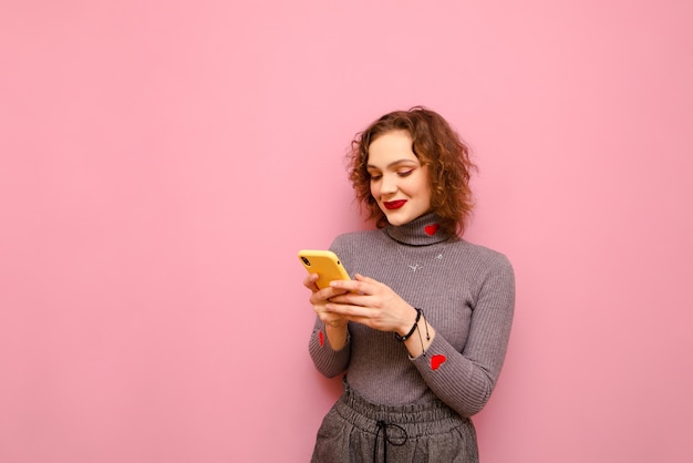 Mulher adolescente bonita com cabelo encaracolado usando a internet em um smartphone