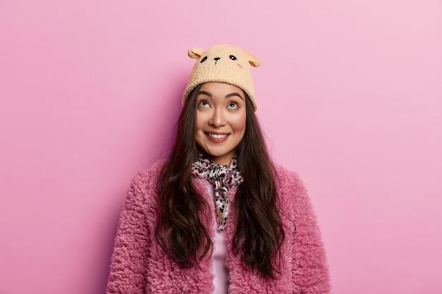 Mulher adolescente bonita e gentil com aparência específica concentrada para cima, tem sorriso dentuço, nota algo agradável acima no teto