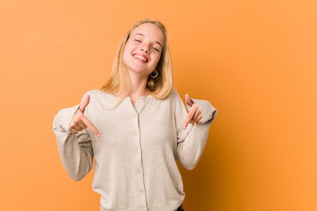 Mulher adolescente bonito e natural aponta para baixo com os dedos