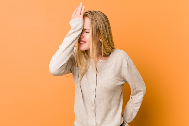 Mulher adolescente bonito e natural, esquecendo algo, batendo na testa com a palma da mão e fechando os olhos.