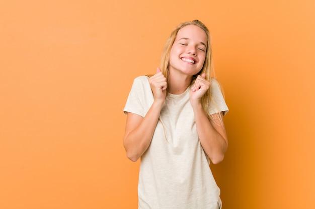 Mulher adolescente bonito e natural, levantando o punho, sentindo-se feliz e bem sucedido