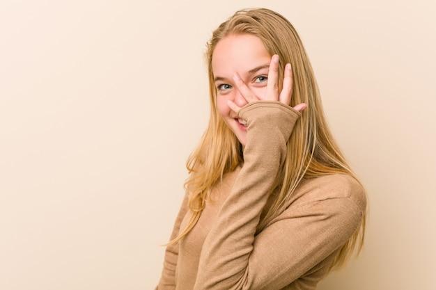 Mulher adolescente bonito e natural piscar entre os dedos, assustada e nervosa.