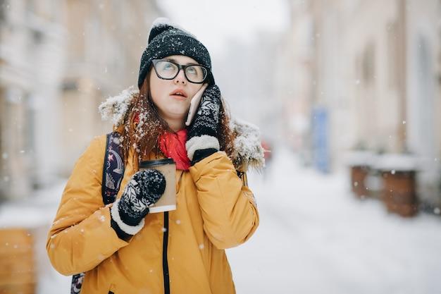 Mulher adolescente caucasiana, falando ao telefone, rindo, segurando um copo de café para viagem sorrindo. retrato de inverno ao ar livre da bela adolescente falando ao telefone