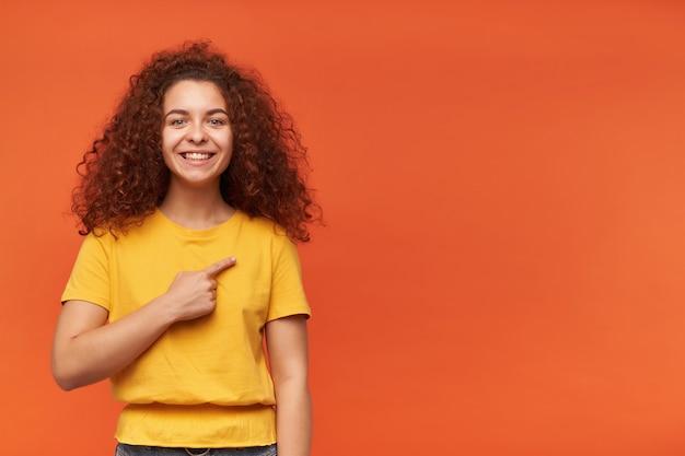 Mulher adolescente com aparência feliz, cabelo ruivo cacheado e camiseta amarela