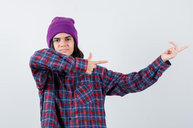 Mulher adolescente com camisa xadrez e gorro apontando para a direita com o dedo indicador e parecendo alegre