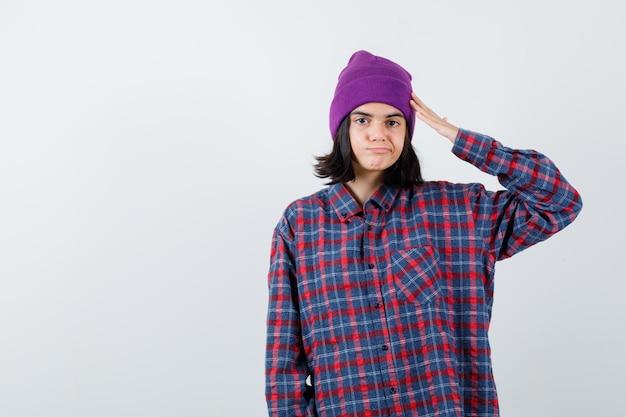 Mulher adolescente com camisa xadrez e gorro roxo mostrando gesto de saudação e parecendo alegre