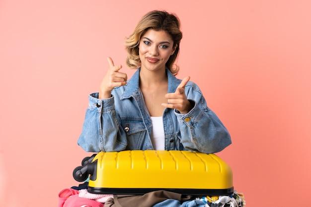 Mulher adolescente com salada isolada em rosa apontando para frente e sorrindo