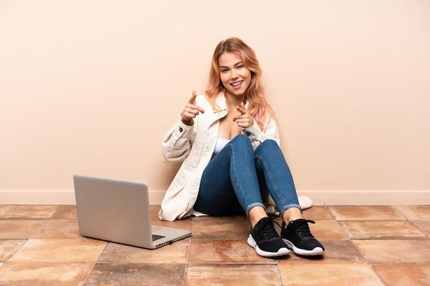 Mulher adolescente com um laptop sentada no chão dentro de casa apontando para a frente e sorrindo